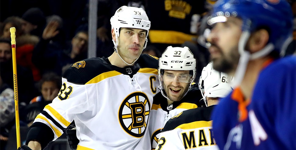 Patrice Bergeron of the Boston Bruins (center) celebrates his hat trick against the New York Islanders with Zdeno Chara and Brad Marchand. (Photo by Bruce Bennett/Getty Images)