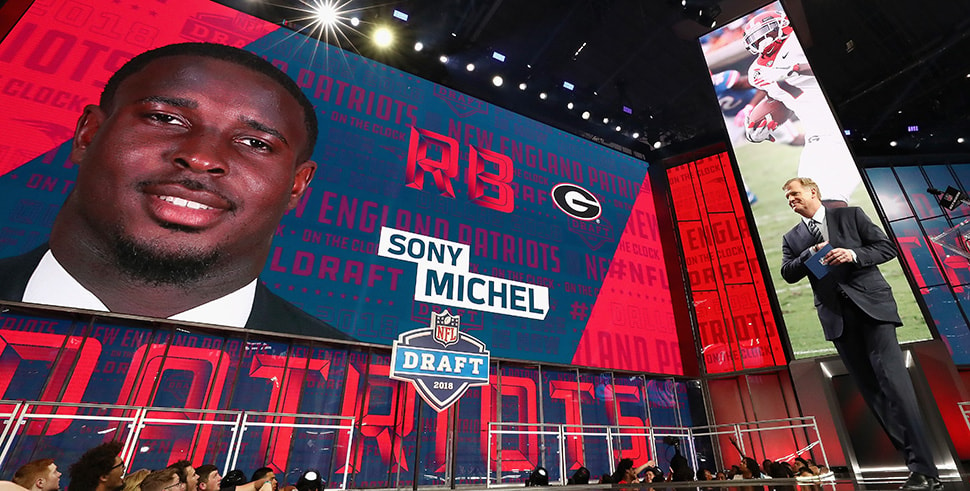 ARLINGTON, TX - APRIL 26: A video board displays an image of Sony Michel of Georgia after he was picked #31 overall by the New England Patriots during the first round of the 2018 NFL Draft at AT&T Stadium on April 26, 2018 in Arlington, Texas. (Photo by Ronald Martinez/Getty Images)