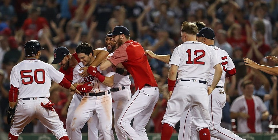 Aug 5, 2018; Boston, MA: The Boston Red Sox players grab left fielder Andrew Benintendi in celebration after his single in the tenth inning completing a four game sweep against the New York Yankees at Fenway Park. (Credit: Paul Rutherford-USA TODAY Sports)