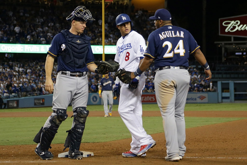 LOS ANGELES, CA - OCTOBER 16, 2018: Manny Machado of the Los Angeles Dodgers and Jesus Aguilar of the Milwaukee Brewers exchange words after Machado's foot hit Aguilar's on his way to being thrown out at first base as catcher Erik Kratz of the Milwaukee Brewers looks on during the tenth inning of Game 4 of the National League Championship Series at Dodger Stadium. (Photo by Jeff Gross/Getty Images)