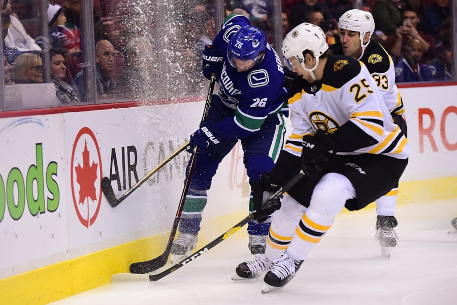 Oct 20, 2018; Vancouver, British Columbia, CAN; Boston Bruins defenseman Brandon Carlo (25) -and Boston Bruins defenseman Zdeno Chara (33) defend against Vancouver Canucks forward Antoine Roussel (26) during the first period at Rogers Arena. Mandatory Credit: Anne-Marie Sorvin-USA TODAY Sports
