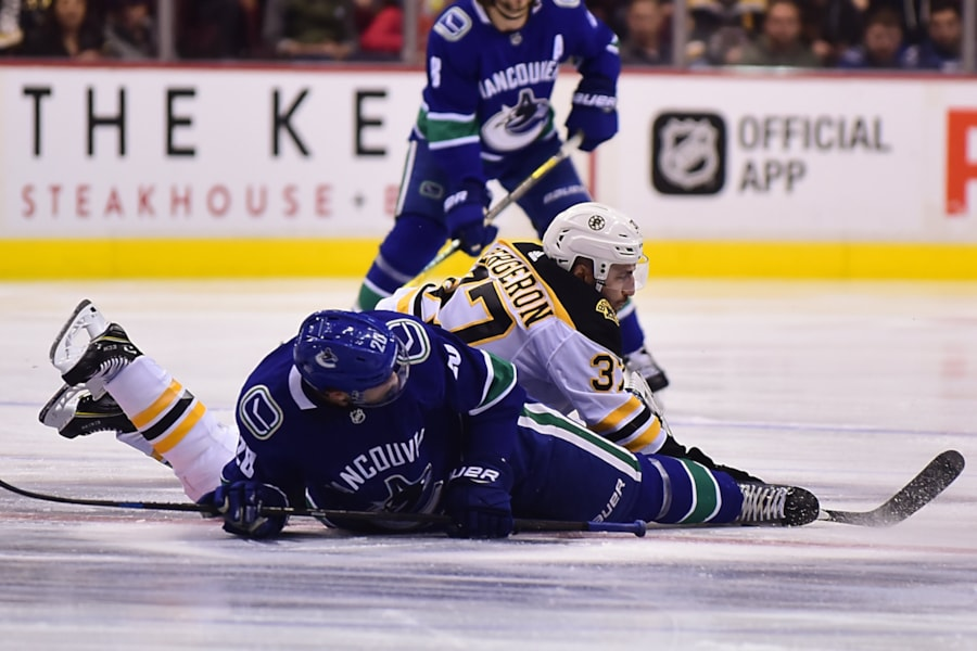 Oct 20, 2018; Vancouver, British Columbia, CAN; Vancouver Canucks forward Brandon Sutter (20) and Boston Bruins forward Patrice Bergeron (37) face off during the first period at Rogers Arena. Mandatory Credit: Anne-Marie Sorvin-USA TODAY Sports