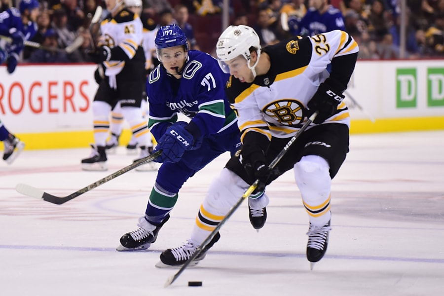 Oct 20, 2018; Vancouver, British Columbia, CAN; Boston Bruins defenseman Brandon Carlo (25) skates with the puck against Vancouver Canucks forward Nikolay Goldobin (77) during the first period at Rogers Arena. Mandatory Credit: Anne-Marie Sorvin-USA TODAY Sports