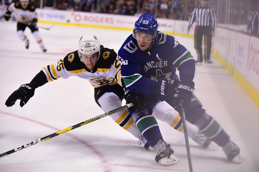 Oct 20, 2018; Vancouver, British Columbia, CAN; Boston Bruins defenseman Brandon Carlo (25) reaches for the puck against Vancouver Canucks forward Bo Horvat (53) during the first period at Rogers Arena. Mandatory Credit: Anne-Marie Sorvin-USA TODAY Sports