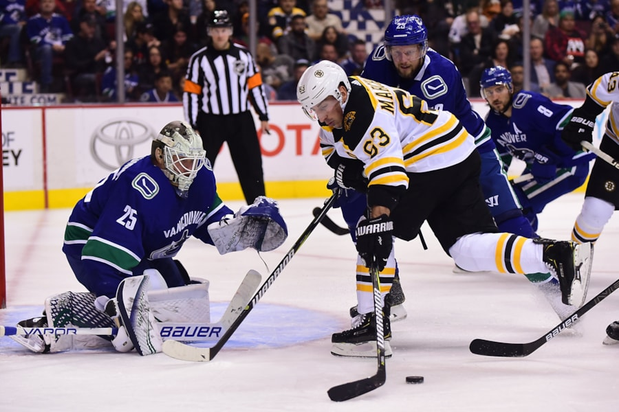 Oct 20, 2018; Vancouver, British Columbia, CAN; Boston Bruins forward Brad Marchand (63) shoots the puck against Vancouver Canucks goaltender Jacob Markstrom (25) and defenseman Alexander Edler (23) during the second period at Rogers Arena. Mandatory Credit: Anne-Marie Sorvin-USA TODAY Sports