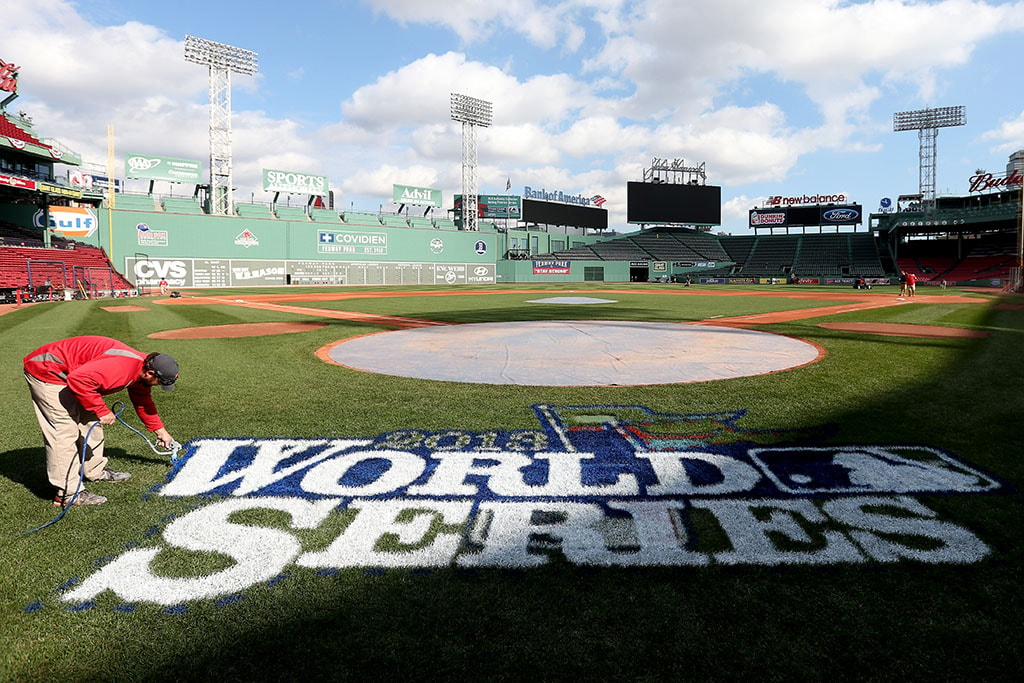BOSTON, MA - OCTOBER 22, 2013: A groundskeeper works on the logo behind home before the start of 2013 World Series Media Day at Fenway Park. The Boston Red Sox won the World Series 4-2 over the St. Louis Cardinals. (Photo by Rob Carr/Getty Images)