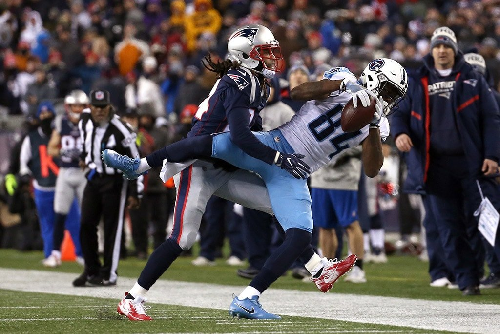 FOXBOROUGH, MA - JANUARY 13: Corey Davis of the Tennessee Titans attempts to hold on to a catch against Stephon Gilmore of the New England Patriots in the first half in the AFC Divisional Playoff game at Gillette Stadium. (Photo by Jim Rogash/Getty Images)
