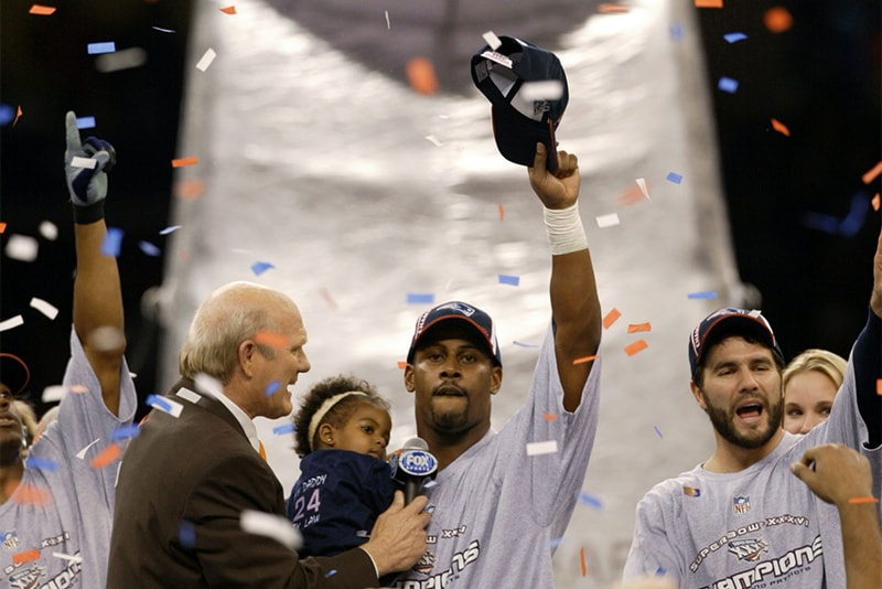 3 Feb 2002: Cornerback Ty Law of the New England Patriots waves to the crowd of fans as sports commentator Terry Bradshaw, left, and teammate Adam Vinatieri, right, look on at the podium after Super Bowl XXXVI. (Brian Bahr/Getty Images)