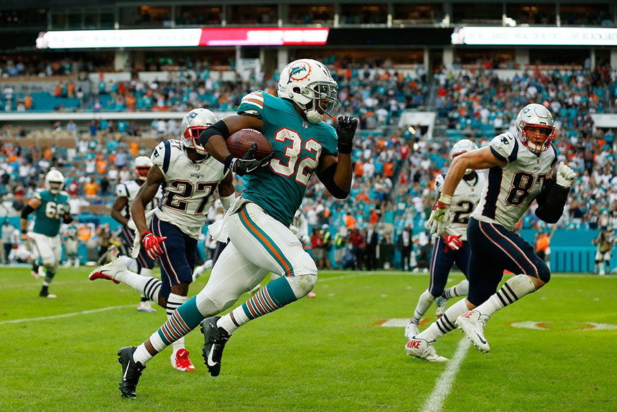 MIAMI, FL - DECEMBER 09: Kenyan Drake #32 of the Miami Dolphins carries the ball for the game winning touchdown during the fourth quarter against the New England Patriots at Hard Rock Stadium on December 9, 2018 in Miami, Florida. (Photo by Michael Reaves/Getty Images)