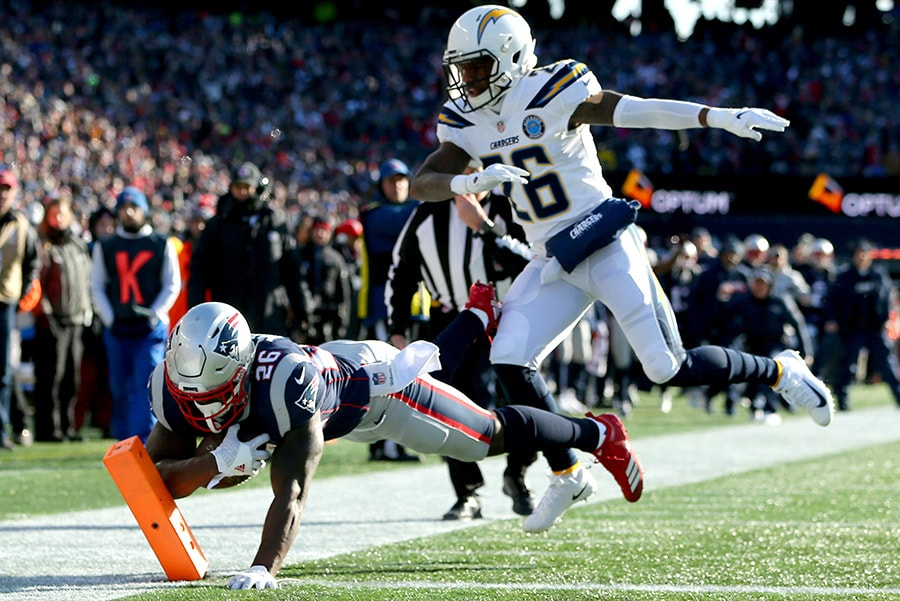 FOXBOROUGH, MASSACHUSETTS - JANUARY 13: Sony Michel of the New England Patriots scores a touchdown as he is defended by Casey Hayward of the Los Angeles Chargers during the first quarter of the AFC Divisional Playoff Game at Gillette Stadium. (Photo by Adam Glanzman/Getty Images)