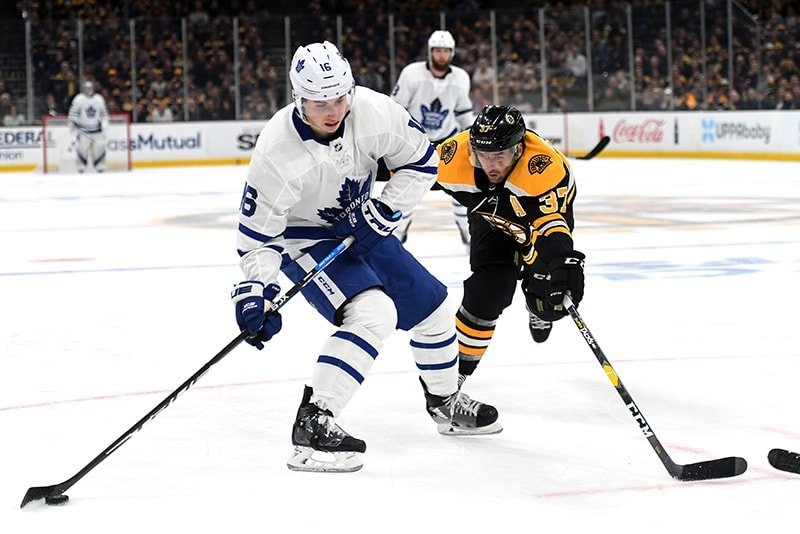Apr 11, 2019; Boston, MA: Toronto Maple Leafs right wing Mitchell Marner controls the puck against Boston Bruins center Patrice Bergeron during the third period in game one of the first round of the 2019 Stanley Cup Playoffs at TD Garden. (Bob DeChiara-USA TODAY Sports)