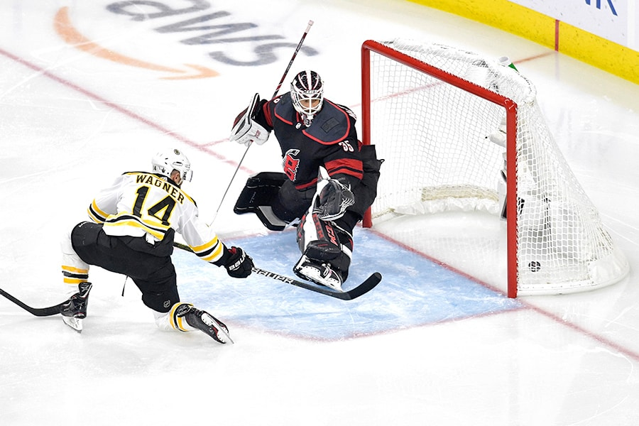 Chris Wagner of the Boston Bruins scores a goal on Curtis McElhinney of the Carolina Hurricanes during the second period in Game 3 of the Eastern Conference Finals during the 2019 NHL Stanley Cup Playoffs at PNC Arena on May 14, 2019 in Raleigh, North Carolina. (Photo by Grant Halverson/Getty Images)