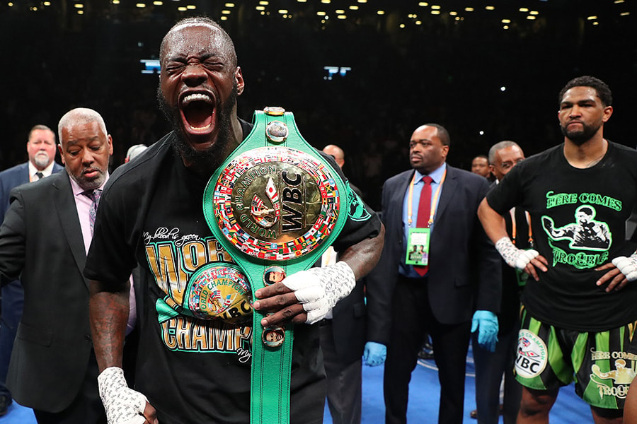 Deontay Wilder celebrates after his first round knockout of Dominic Breazeale who looks on in the first round during their bout for Wilder's WBC heavyweight title at Barclays Center on May 18, 2019 in New York City. (Photo by Al Bello/Getty Images)