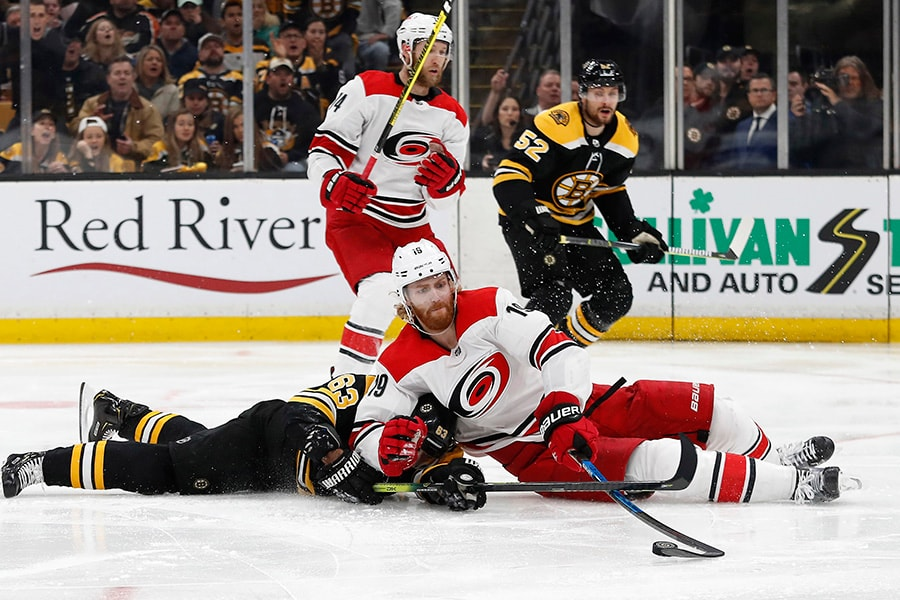 May 12, 2019; Boston, MA: Carolina Hurricanes defenseman Dougie Hamilton tries to control the puck after falling on Boston Bruins left wing Brad Marchand during the second period in Game 2 of the Eastern Conference Final of the 2019 Stanley Cup Playoffs at TD Garden. (Winslow Townson-USA TODAY Sports)