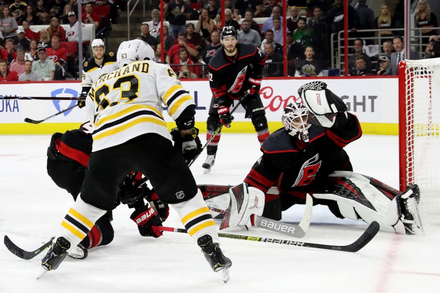 RALEIGH, NORTH CAROLINA - MAY 16: Curtis McElhinney #35 of the Carolina Hurricanes makes a glove save against Brad Marchand #63 of the Boston Bruins during the first period in Game Four of the Eastern Conference Finals during the 2019 NHL Stanley Cup Playoffs at PNC Arena on May 16, 2019 in Raleigh, North Carolina. (Photo by Bruce Bennett/Getty Images)
