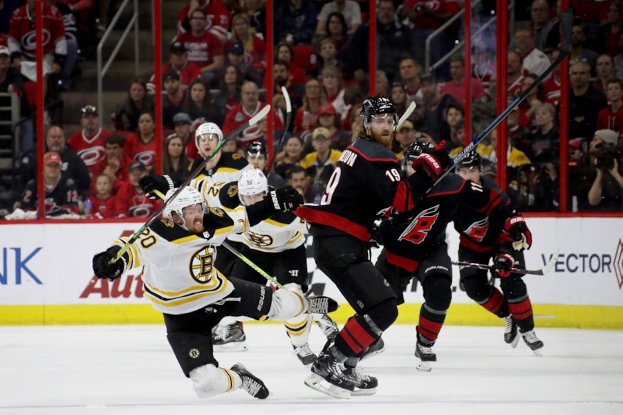 RALEIGH, NORTH CAROLINA - MAY 16: Joakim Nordstrom #20 of the Boston Bruins falls to the ice after colliding with Dougie Hamilton #19 of the Carolina Hurricanes during the second period in Game Four of the Eastern Conference Finals during the 2019 NHL Stanley Cup Playoffs at PNC Arena on May 16, 2019 in Raleigh, North Carolina. (Photo by Bruce Bennett/Getty Images)
