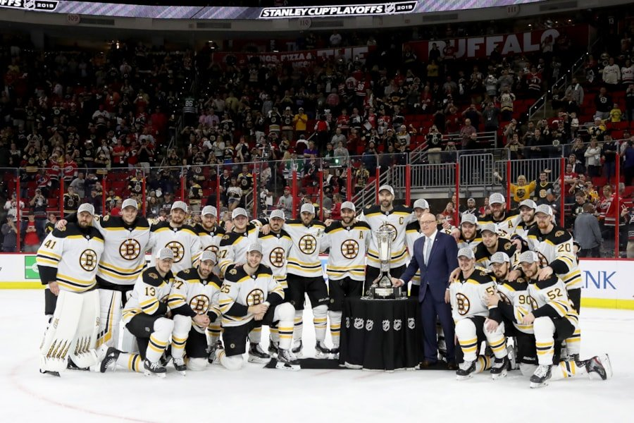 RALEIGH, NORTH CAROLINA - MAY 16: The Boston Bruins pose with the Deputy Commissioner Bill Daly and the Prince of Wales Trophy after defeating the Carolina Hurricanes in Game Four to win the Eastern Conference Finals during the 2019 NHL Stanley Cup Playoffs at PNC Arena on May 16, 2019 in Raleigh, North Carolina. (Photo by Bruce Bennett/Getty Images)