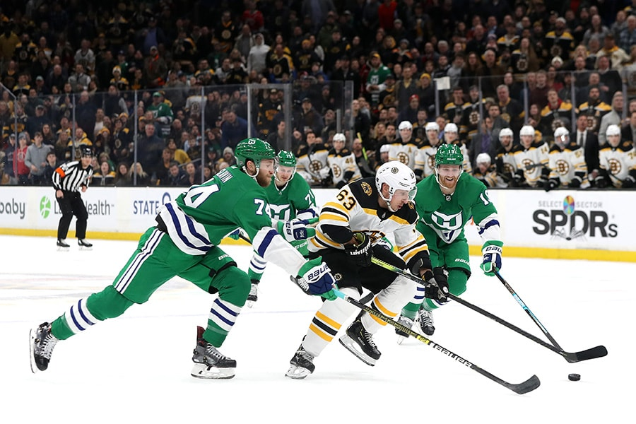Jaccob Slavin of the Carolina Hurricanes and Dougie Hamilton defend Brad Marchand of the Boston Bruins during the first period at TD Garden on March 05, 2019 in Boston, Massachusetts. (Photo by Maddie Meyer/Getty Images)