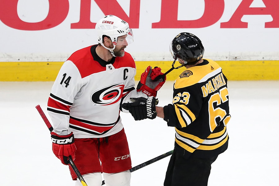 Justin Williams of the Carolina Hurricanes pulls on the chinstrap of Brad Marchand of the Boston Bruins during the second period in Game 2 of the Eastern Conference Final during the 2019 NHL Stanley Cup Playoffs at TD Garden on May 12, 2019 in Boston, Massachusetts. (Photo by Adam Glanzman/Getty Images)