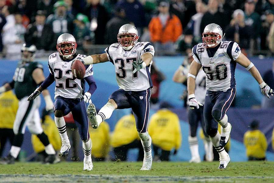 Rodney Harrison, Asante Samuel (#22), and Mike Vrabel (#50) of the New England Patriots celebrate after defeating the Philadelphia Eagles in Super Bowl XXXIX at Alltel Stadium on February 6, 2005 in Jacksonville, Florida. The Patriots defeated the Eagles 24-21. (Photo by Brian Bahr/Getty Images)