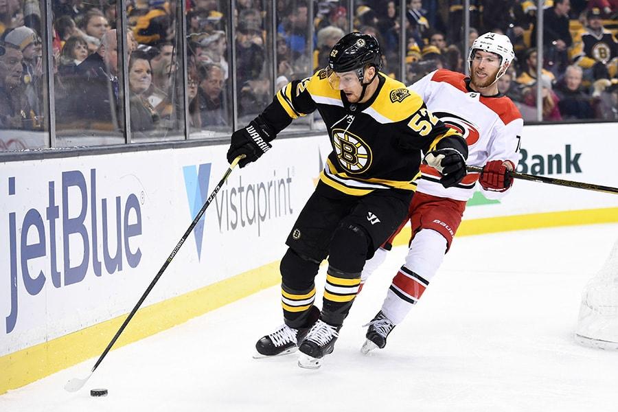 Jan 6, 2018; Boston, MA: Boston Bruins center Sean Kuraly controls the puck in front of Carolina Hurricanes defenseman Jaccob Slavin during the third period at TD Garden. (Bob DeChiara-USA TODAY Sports)