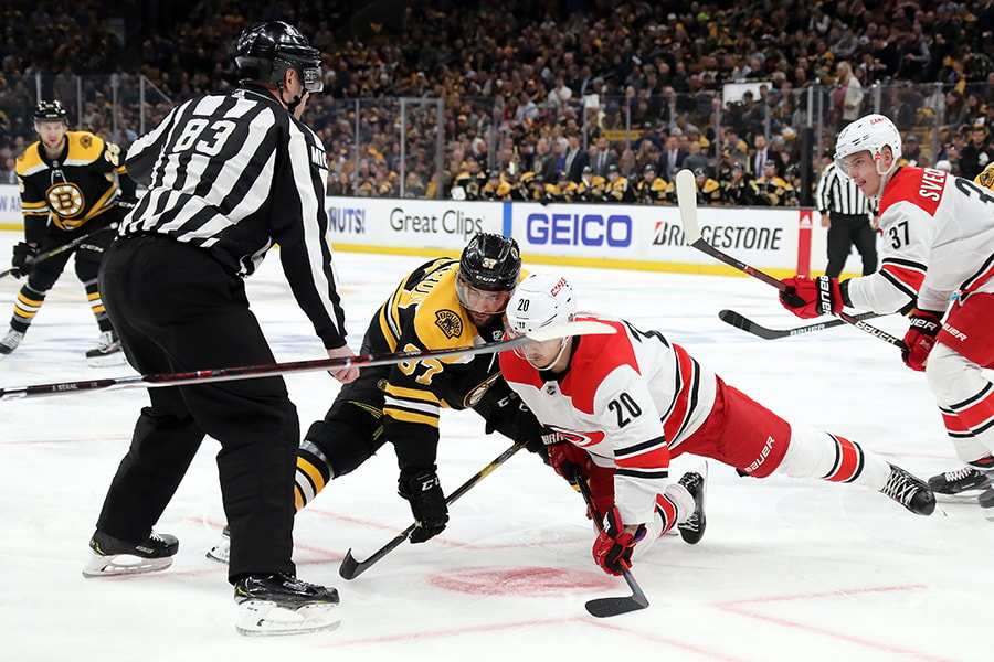Patrice Bergeron of the Boston Bruins and Sebastian Aho of the Carolina Hurricanes battle for the puck during a face-off in the first period during Game 1 of the Eastern Conference Final during the 2019 NHL Stanley Cup Playoffs at TD Garden on May 09, 2019 in Boston, Massachusetts. (Photo by Bruce Bennett/Getty Images)