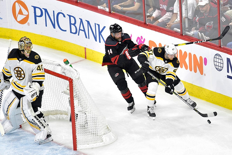 Torey Krug of the Boston Bruins skates with the puck behind the net against Justin Williams of the Carolina Hurricanes during the first period in Game 3 of the Eastern Conference Finals during the 2019 NHL Stanley Cup Playoffs at PNC Arena on May 14, 2019 in Raleigh, North Carolina. (Photo by Grant Halverson/Getty Images)