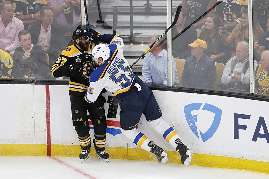 Patrice Bergeron of the Boston Bruins is checked into the boards by Colton Parayko of the St. Louis Blues during the first period in Game 7 of the 2019 NHL Stanley Cup Final at TD Garden on June 12, 2019 in Boston, Massachusetts. (Photo by Patrick Smith/Getty Images)