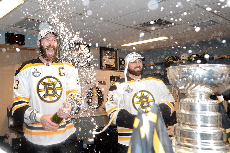 Shane Hnidy and Zdeno Chara of the Boston Bruins celebrate in the locker room after defeating the Vancouver Canucks in Game Seven of the 2011 NHL Stanley Cup Final at Rogers Arena on June 15, 2011 in Vancouver, British Columbia, Canada. The Boston Bruins defeated the Vancouver Canucks 4-0. (Photo by Harry How/Getty Images)