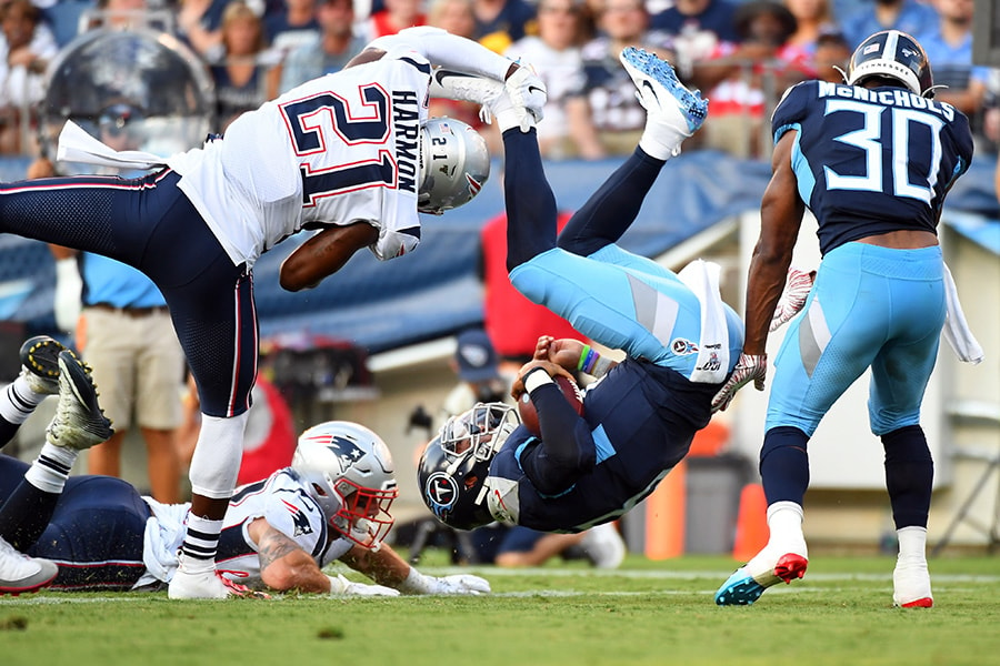 Aug 17, 2019; Nashville, TN: Tennessee Titans quarterback Marcus Mariota is flipped by New England Patriots strong safety Duron Harmon as he scores on a two point conversion during the first half at Nissan Stadium. (Christopher Hanewinckel-USA TODAY Sports)