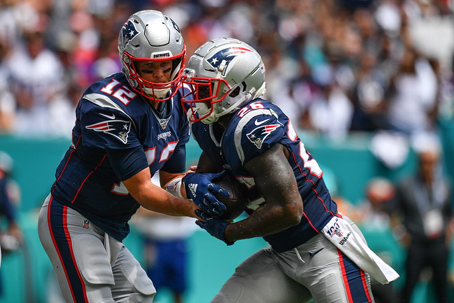 Tom Brady of the New England Patriots hands the ball to Sony Michel of the New England Patriots for a touchdown in the first quarter against the Miami Dolphins at Hard Rock Stadium on September 15, 2019 in Miami, Florida. (Photo by Mark Brown/Getty Images)