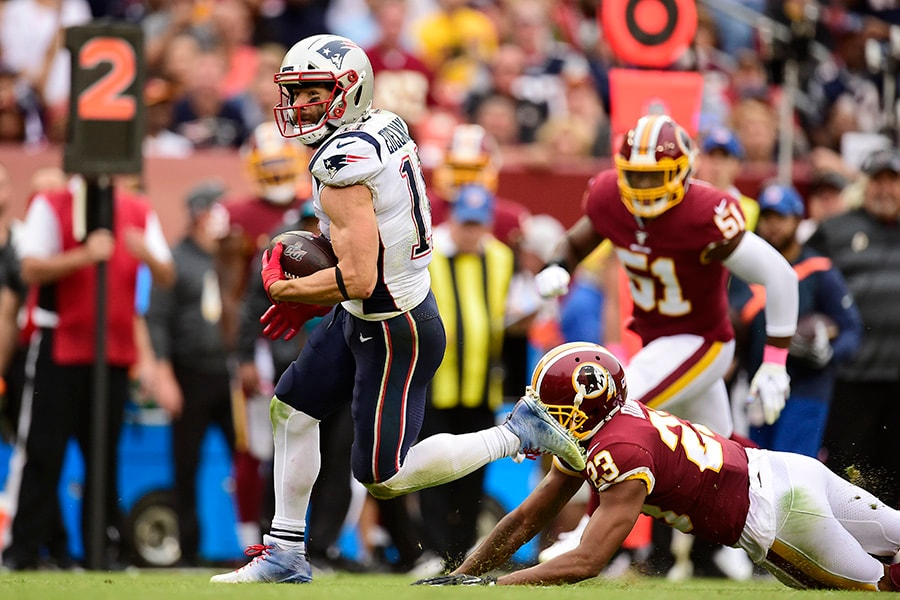 Julian Edelman of the New England Patriots avoids the tackle of Quinton Dunbar of the Washington Redskins in the third quarter at FedExField on October 6, 2019 in Landover, Maryland. (Photo by Patrick McDermott/Getty Images)