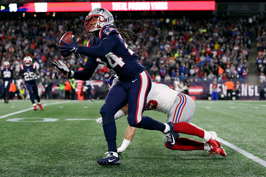 Oct 10, 2019; Foxborough, MA: New England Patriots cornerback Stephon Gilmore makes a catch in front of New York Giants tight end Garrett Dickerson during the second half at Gillette Stadium. (Paul Rutherford-USA TODAY Sports)
