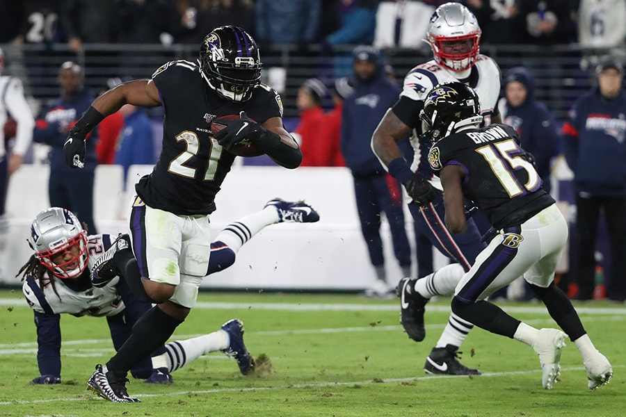 Running back Mark Ingram II of the Baltimore Ravens rushes past cornerback Stephon Gilmore of the New England Patriots in the first half at M&T Bank Stadium on November 3, 2019 in Baltimore, Maryland. (Photo by Todd Olszewski/Getty Images)