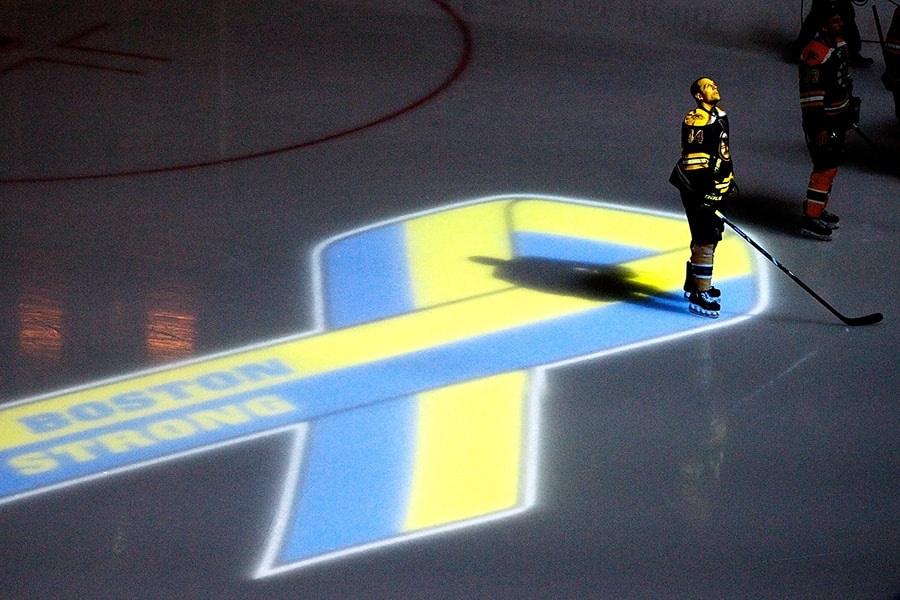 Dennis Seidenberg of the Boston Bruins stands near aa projection of the Boston Marathon Memorial Ribbon seen on the ice during pre game ceremonies in remembrance of the Boston Marathon bombing victims before a game between the Buffalo Sabres and the Boston Bruins at TD Garden on April 17, 2013 in Boston, Massachusetts. (Photo by Jim Rogash/Getty Images)