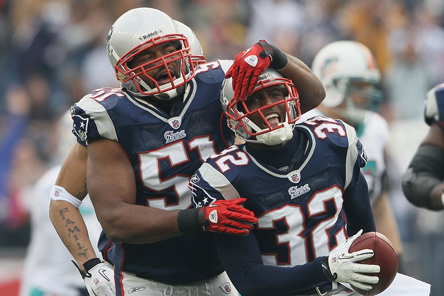 Devin McCourty of the New England Patriots is congratulated by teammate Jerod Mayo after McCourty intercepted a pass by the Miami Dolphins on January 2, 2011 at Gillette Stadium in Foxboro, Massachusetts. (Photo by Elsa/Getty Images)