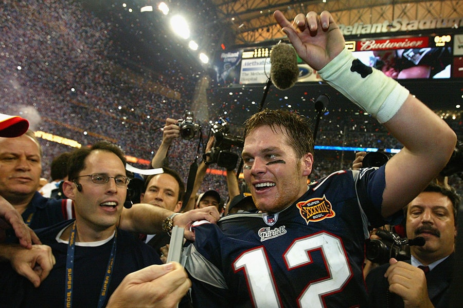 MVP Tom Brady of the New England Patriots celebrates after defeating the Carolina Panthers 32-29 in Super Bowl XXXVIII at Reliant Stadium on February 1, 2004 in Houston, Texas. (Photo by Andy Lyons/Getty Images)