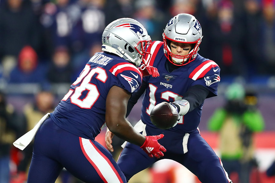 Tom Brady of the New England Patriots looks to hand off to Sony Michel during the first half against the Kansas City Chiefs in the game at Gillette Stadium on December 08, 2019 in Foxborough, Massachusetts. (Photo by Adam Glanzman/Getty Images)