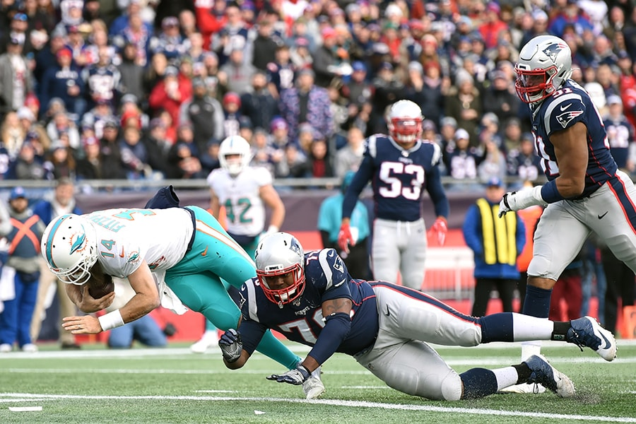 Dec 29, 2019; Foxborough, Massachusetts, USA; Miami Dolphins quarterback Ryan Fitzpatrick (14) runs for a touchdown past New England Patriots defensive tackle Adam Butler (70) during the xx half at Gillette Stadium. Mandatory Credit: Bob DeChiara-USA TODAY Sports