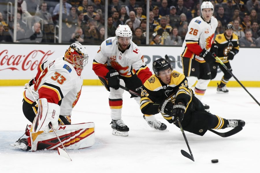 Feb 25, 2020; Boston, Massachusetts, USA; Calgary Flames defenseman TJ Brodie (7) gets a penalty for tripping Boston Bruins left wing Brad Marchand (63) in front of Calgary Flames goaltender David Rittich (33) during the first period at TD Garden. Mandatory Credit: Winslow Townson-USA TODAY Sports
