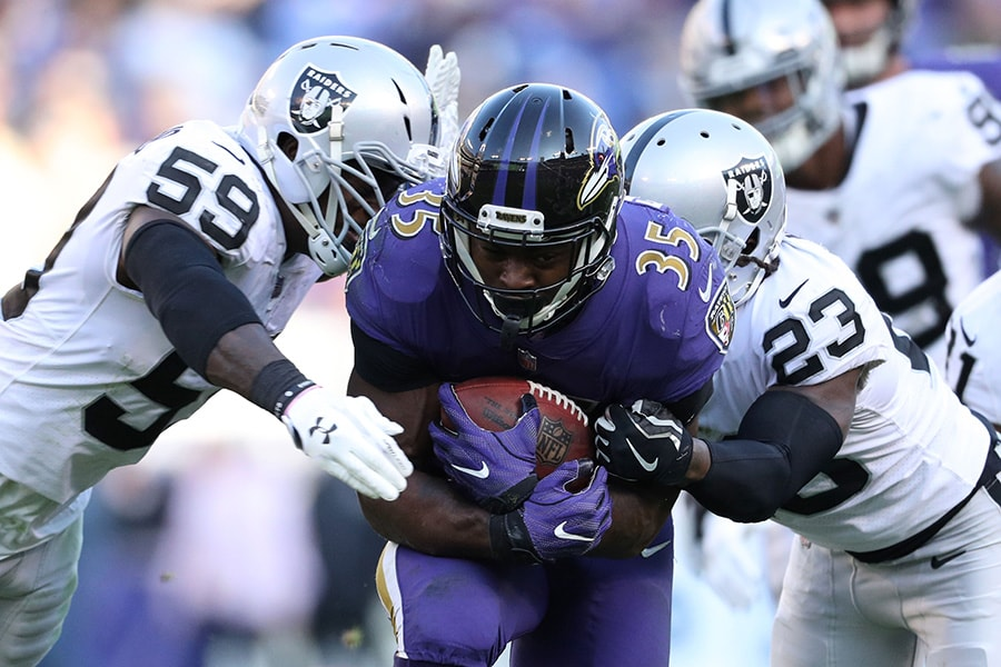 BALTIMORE, MARYLAND - NOVEMBER 25: Running Back Gus Edwards #35 of the Baltimore Ravens is tackled as he carries the ball by cornerback Nick Nelson #23 and outside linebacker Tahir Whitehead #59 of the Oakland Raiders in the third quarter at M&T Bank Stadium on November 25, 2018 in Baltimore, Maryland. (Photo by Patrick Smith/Getty Images)