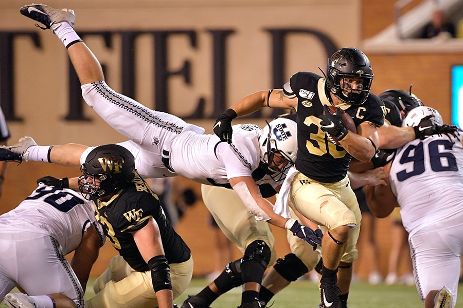 WINSTON SALEM, NORTH CAROLINA - AUGUST 30: David Woodward #9 of the Utah State Aggies dives to tackle Cade Carney #36 of the Wake Forest Demon Deacons during the first half of their game at BB&T Field on August 30, 2019 in Winston Salem, North Carolina. (Photo by Grant Halverson/Getty Images)