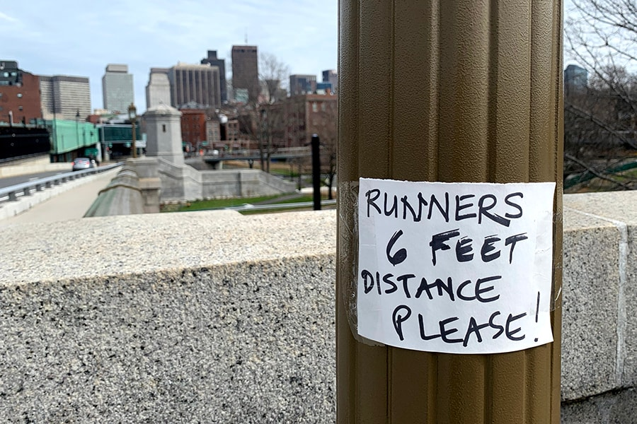 BOSTON, MASSACHUSETTS - APRIL 08: A sign on the Longfellow Bridge encourages social distance among runners on April 08, 2020 in Boston, Massachusetts. A stay-at-home order by by Gov. Charlie Baker is in effect through May 4, while Boston Mayor Marty Walsh has enacted a recommended curfew of 9 p.m. and is encouraging the use of face masks in public spaces. (Photo by Maddie Meyer/Getty Images)