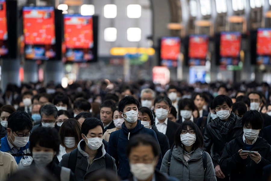 TOKYO, JAPAN - MARCH 26: Commuters wearing face masks make their way to work on March 26, 2020 in Tokyo, Japan. Tokyo Governor Yuriko Koike held a press conference last night to request citizens to refrain from going outside this weekend for nonessential reasons after 41 cases of new coronavirus infections were confirmed yesterday. She warned that Tokyo, one of the largest and most densely populated cities on earth, could face a lockdown if there is a surge in new coronavirus cases. (Photo by Tomohiro Ohsumi/Getty Images)
