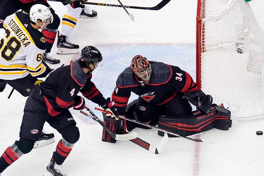 Aug 15, 2020; Toronto, Ontario, CAN; Boston Bruins center Jack Studnicka (68), Carolina Hurricanes defenseman Haydn Fleury (4) and goaltender Petr Mrazek (34) reach for the loose puck during the first period in game three of the first round of the 2020 Stanley Cup Playoffs at Scotiabank Arena. Mandatory Credit: John E. Sokolowski-USA TODAY Sports