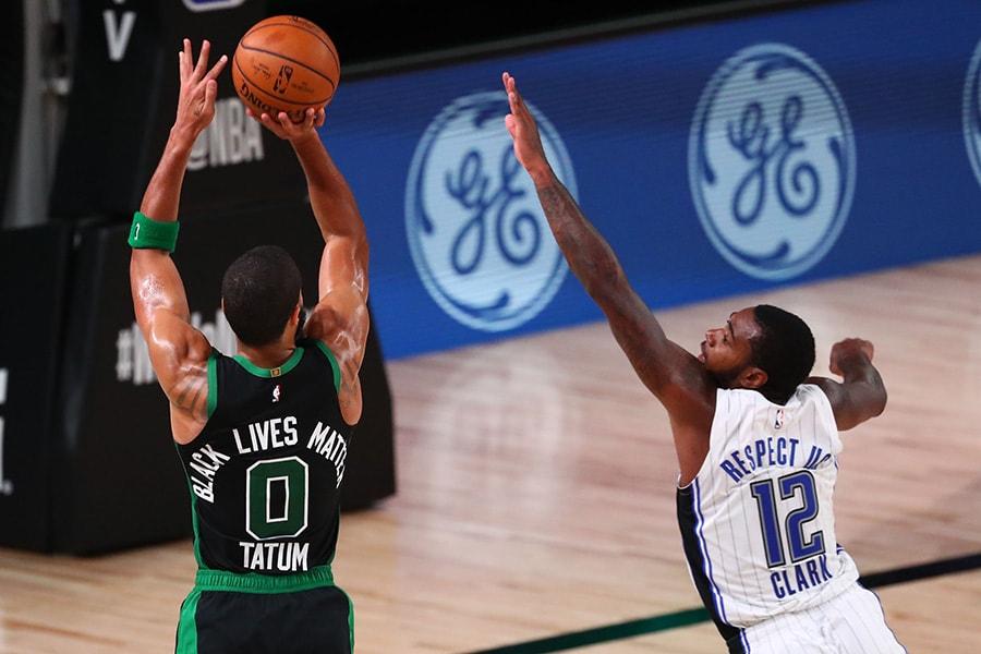 Aug 9, 2020; Lake Buena Vista, Florida, USA; Boston Celtics forward Jayson Tatum (0) makes a three pointer over Orlando Magic forward Gary Clark (12) in the fourth quarter of a NBA basketball game at AdventHealth Arena. Mandatory Credit: Kim Klement-USA TODAY Sports