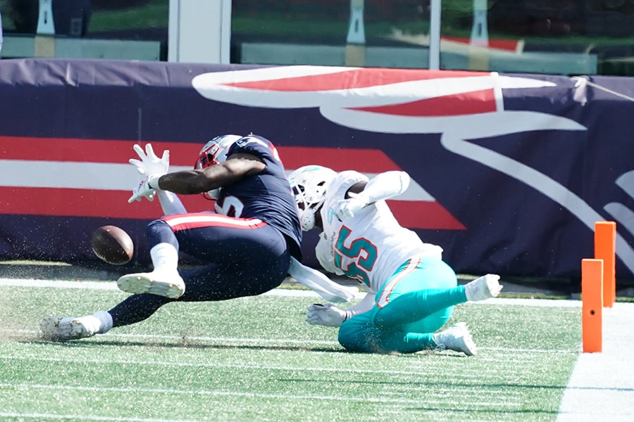 Sep 13, 2020; Foxborough, Massachusetts, USA; New England Patriots wide receiver N'Keal Harry (15) fumbles the ball in the end zone for a touchback as Miami Dolphins outside linebacker Jerome Baker (55) defends at Gillette Stadium. Mandatory Credit: David Butler II-USA TODAY Sports