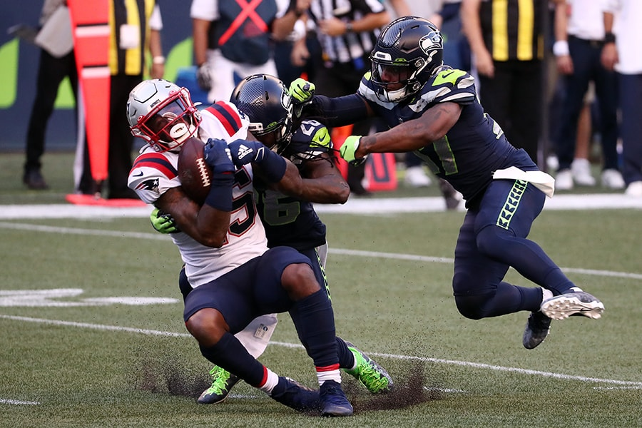 SEATTLE, WASHINGTON - SEPTEMBER 20: N'Keal Harry #15 of the New England Patriots is tackled by Shaquill Griffin #26 and Quandre Diggs #37 of the Seattle Seahawks during the first half at CenturyLink Field on September 20, 2020 in Seattle, Washington. (Photo by Abbie Parr/Getty Images)