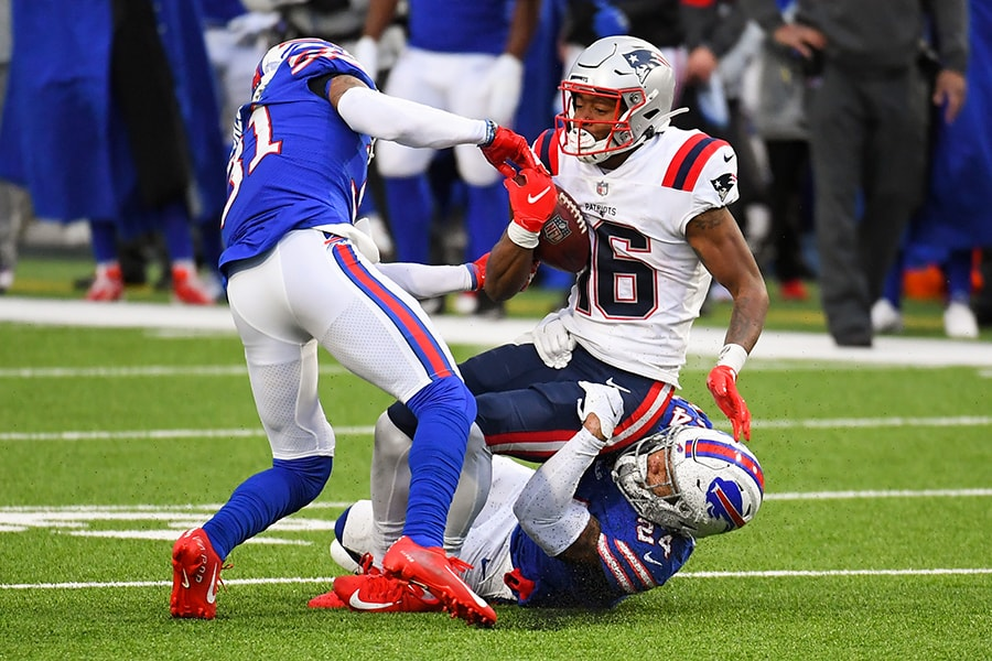 Nov 1, 2020; Orchard Park, New York, USA; Buffalo Bills strong safety Dean Marlowe (31) moves in to strip the ball from New England Patriots wide receiver Jakobi Meyers (16) as cornerback Taron Johnson (24) makes the tackle during the third quarter at Bills Stadium. Mandatory Credit: Rich Barnes-USA TODAY Sports