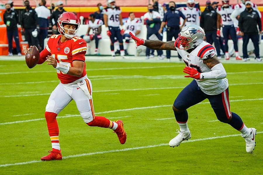 Oct 5, 2020; Kansas City, Missouri, USA; Kansas City Chiefs quarterback Patrick Mahomes (15) rolls out to pass as New England Patriots linebacker Anfernee Jennings(58) defends at Arrowhead Stadium. Mandatory Credit: Jay Biggerstaff-USA TODAY Sports